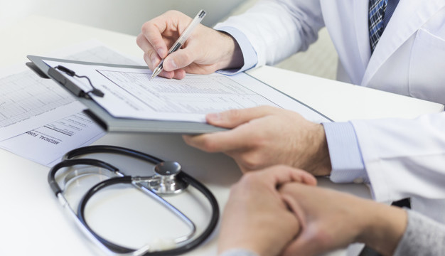 close-up-doctor-filling-medical-form-with-patient_23-2148050550